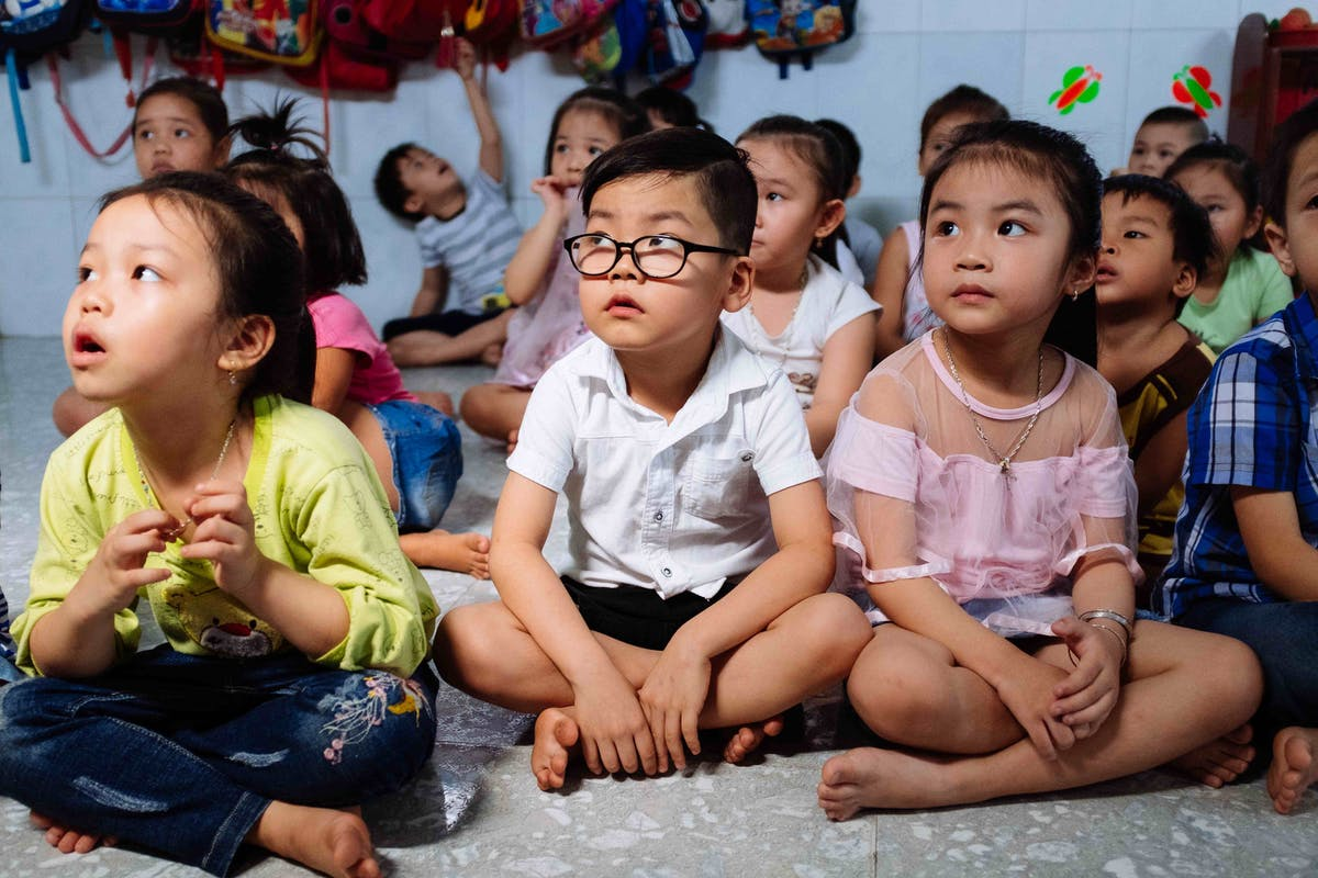 Cataract patient Tam, 5 years, sits in a school lesson after surgery on his bilateral cataracts