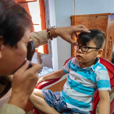 Orbis-trained ophthalmologist Dr.Lai checks Tam's eyes following eye surgery