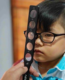 Vietnam 2018 C Louis Leeson Binh Dinh Tam M 5Yrs Cataract Screening Portrait03 Retinoscopy Rack