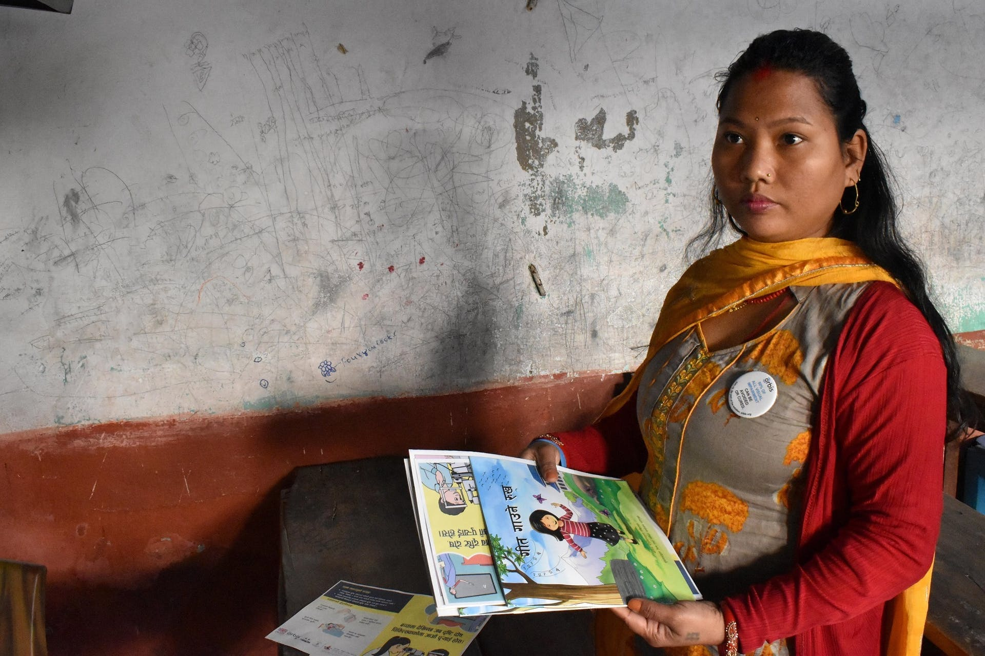 A teacher in Nepal with her copy of The Singing Tree during a REACH school screening program