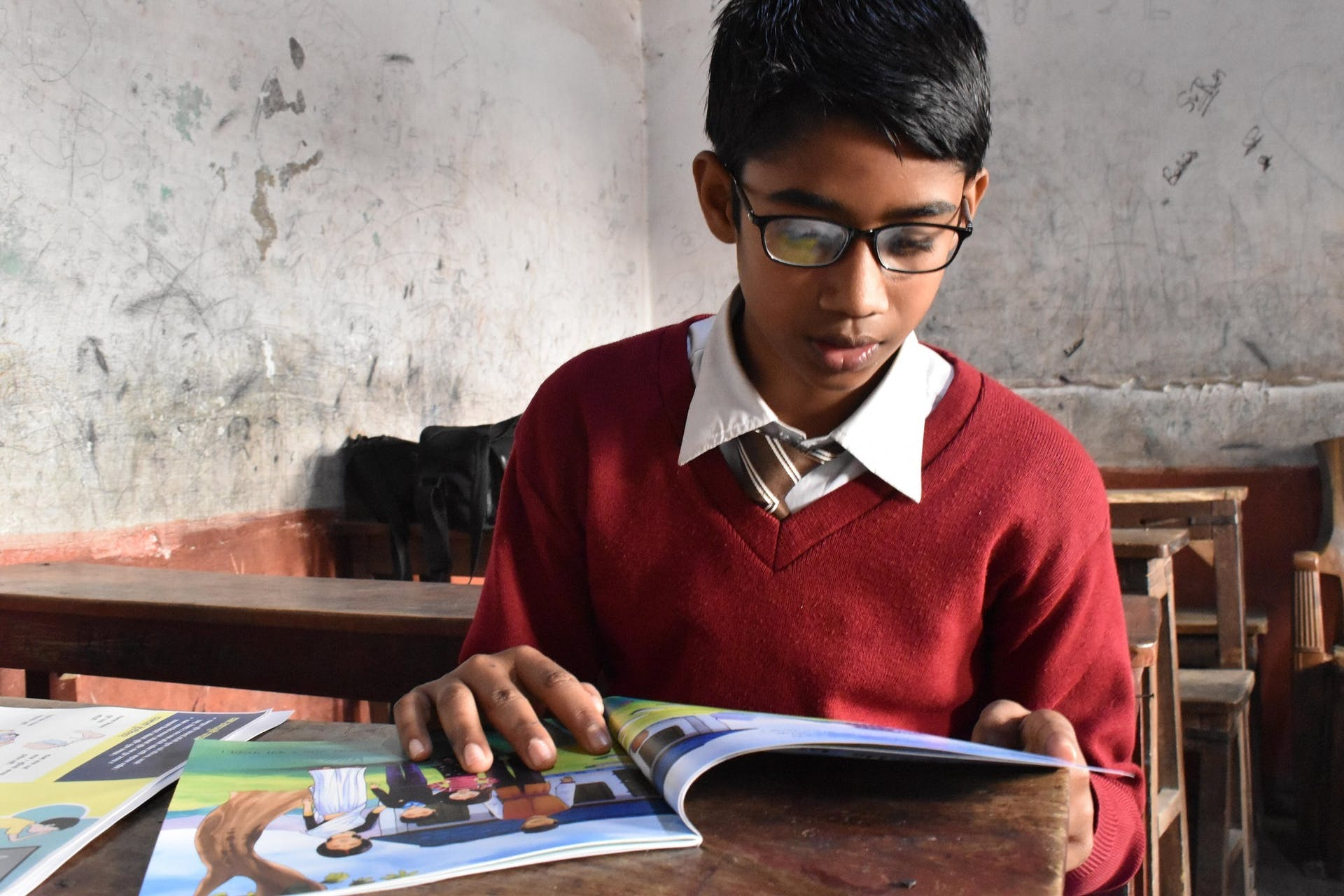 A school boy reads his copy of the Singing Tree in Nepal