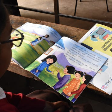 A school girl reads her copy of The Singing Tree in Nepal